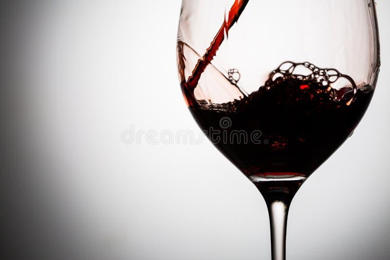No vidro bonito o vinho tinto derramado com ondas e espirra fotografia de stock