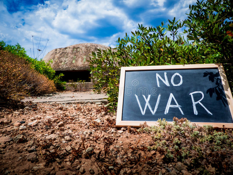 No war. The message & x22;no war& x22; written on a chalkboard. this one is in front of an italian military installation of the second world war, over the coast stock images