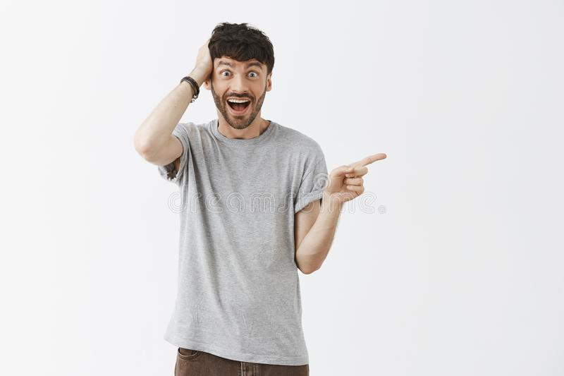 No way it cannot be true. Portrait of amazed and thrilled happy and excited good-looking young artistic guy in grey t royalty free stock photo