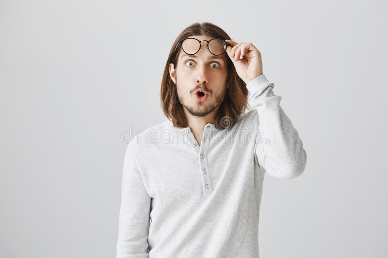 No way, cannot believe my own eyes. Studio shot of shocked and amazed handsome modern guy with beard and long hair stock image