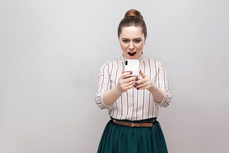 No way! Portrait of shocked attractive blogger young woman wearing in striped shirt standing, using smartphone and watching video. With amazed face. Indoor stock images