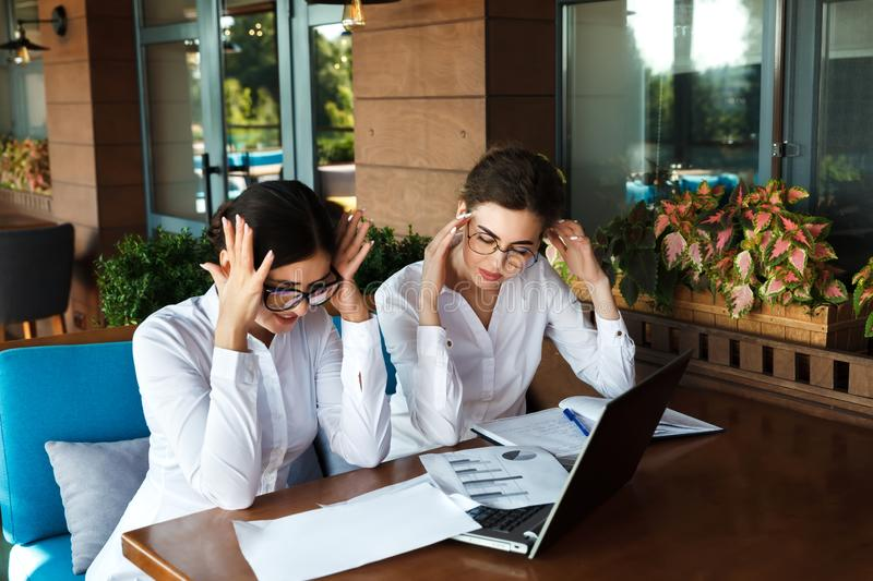 No way! Shocked and tired businesswomen having headache. royalty free stock images