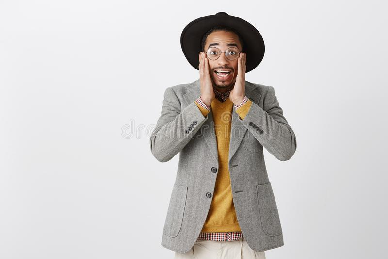 No way, what shocking rumor. Indoor shot of surprised handsome dark-skinned entrepreneur in stylish glasses, outfit and. Hat, holding palms on cheeks, popping royalty free stock images