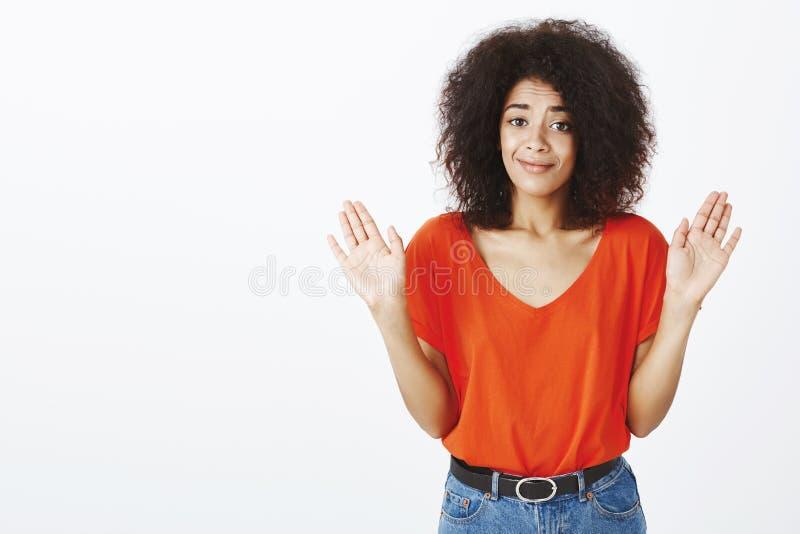 No wini ja Portret nieświadoma piękna afroamerykańska dziewczyna z afro ostrzyżeniem, smirking przy kamerą, podnosi palmy zdjęcie stock