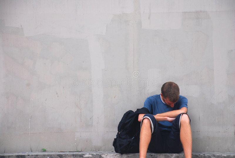 No Work. A young man, depressed and sitting on a street corner with a backpack royalty free stock photos