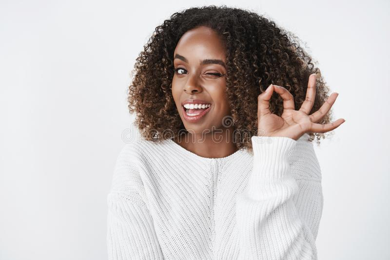 No worries I got it under control. Relaxed and unbothered confident good-looking successful african american woman. Winking cheeky and smiling as showing okay stock photo