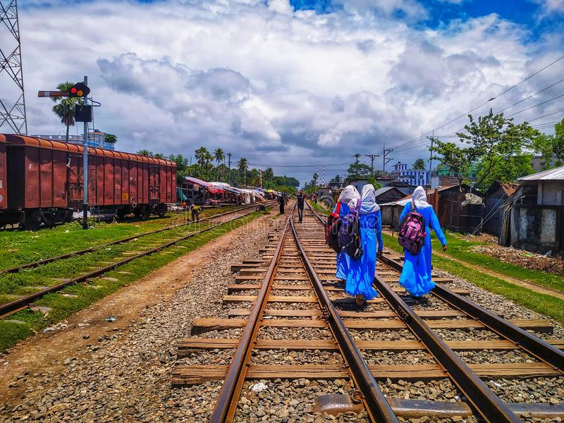 Noapara火车站,Noapar,Jashore,孟加拉国:2019年7月27日:长的铁路线、人们和两个女孩有佩带Sch的袋子的 免版税库存图片