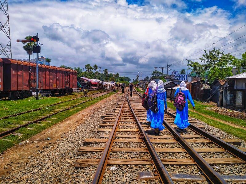 Noapara järnvägsstation, Noapar, Jashore, Bangladesh: Juli 27, 2019: Lång stånglinje, folk och två flickor med påsar som bär Sch royaltyfria bilder
