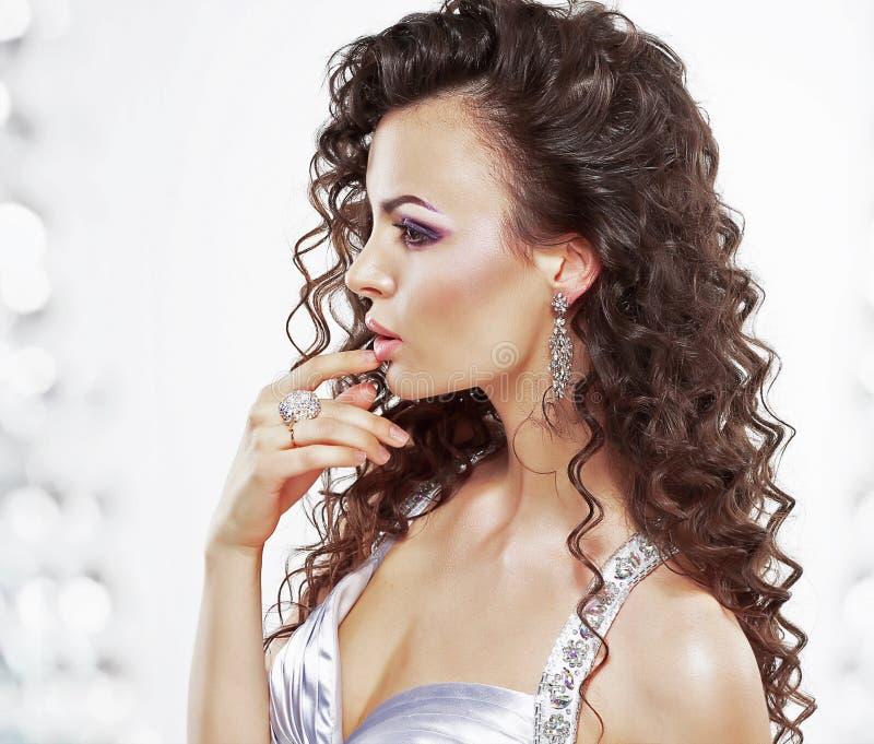 Noble elegante Frau mit Schmuck - Platin-Ring und Ohrringe. Krause Frisur stockfoto
