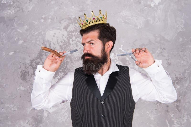Noble worker. Crown award. Barber shop concept. Bearded hipster shaving. Vintage barber. Barber tools. Barber hold royalty free stock photography