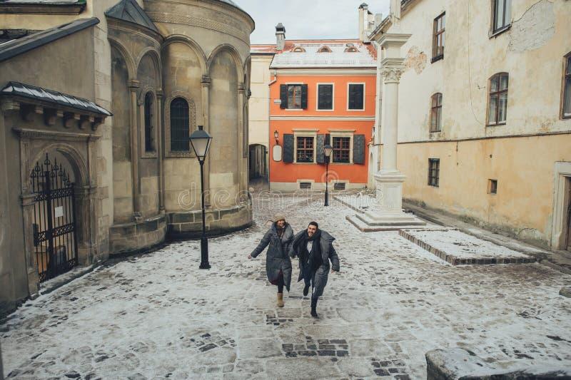 Nobler Bräutigam und seine herrliche Braut werfen draußen in den Wintermänteln auf stockfotos