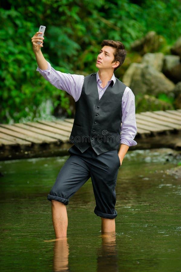 Nobler junger Mann, der ein selfie im See nimmt stockfoto