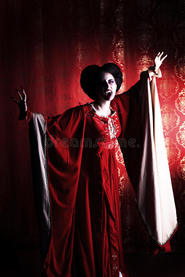 Noblewoman. Portrait of a bloodthirsty female vampire over red vintage background royalty free stock image