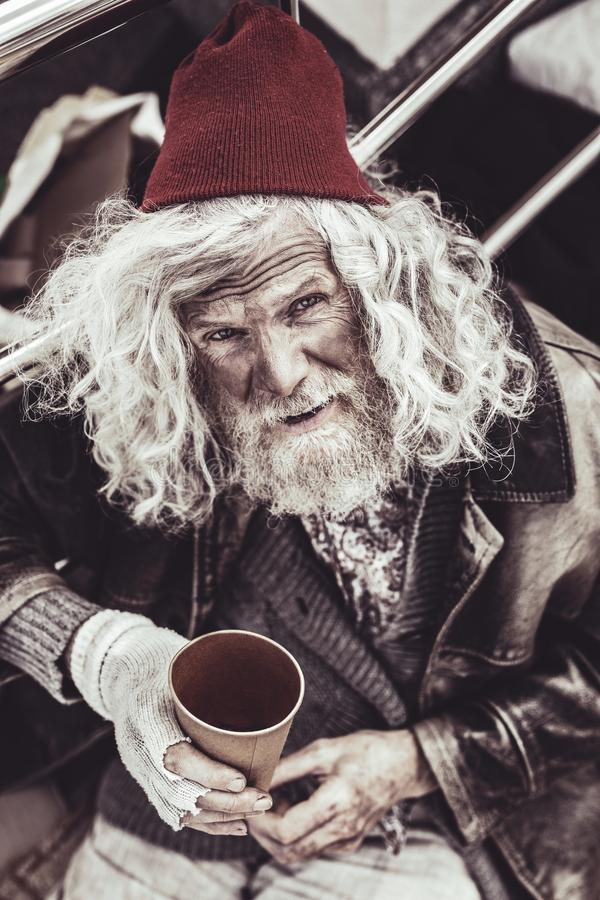 Nobody throwing money in plastic cup for beggar. royalty free stock images