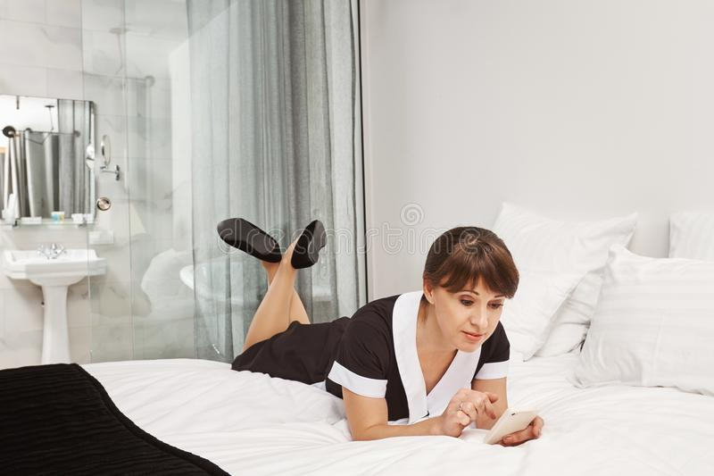 Nobody will notice that I am taking break. Portrait of relaxed housemaid lying in uniform on bed, browsing in social royalty free stock photo