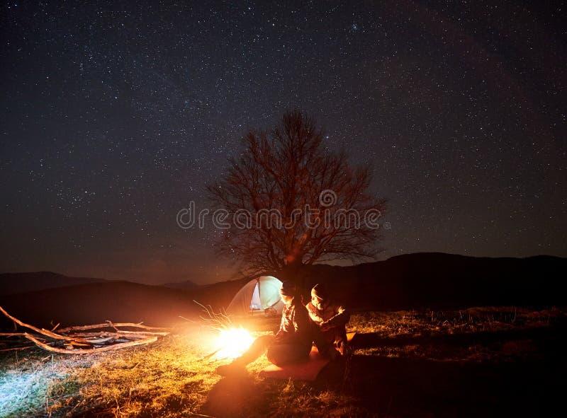 Noc camping w górach Para wycieczkowicze ma spoczynkowego pobliskiego ognisko, turystyczny namiot pod gwiaździstym niebem obrazy royalty free