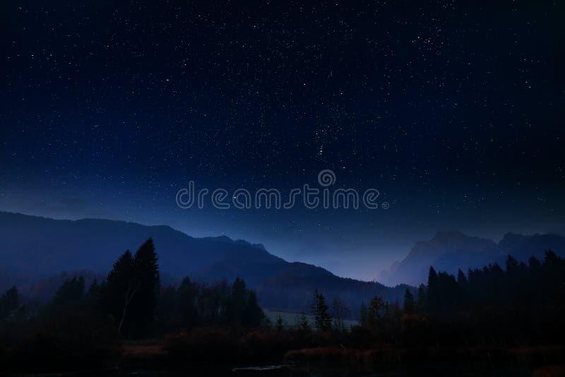 Noc krajobraz z ciemnym niebem i gwiazdami w Slovenia, natura w Europa Mgłowi Triglav Alps z lasem, podróż w Slovenia obrazy stock