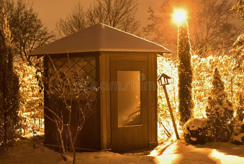 Noc obrazek zaokrąglony ogródu dom w zima czasie zakrywającym śnieżnym i zaświecającym latarnią uliczną z pomarańczowym światłem zdjęcie royalty free