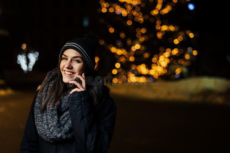 Noc portret piękna brunetki kobieta używa smartphone podczas zimnej zimy w parku Zimy radość chłopiec wakacji lay śniegu zima poz obraz royalty free