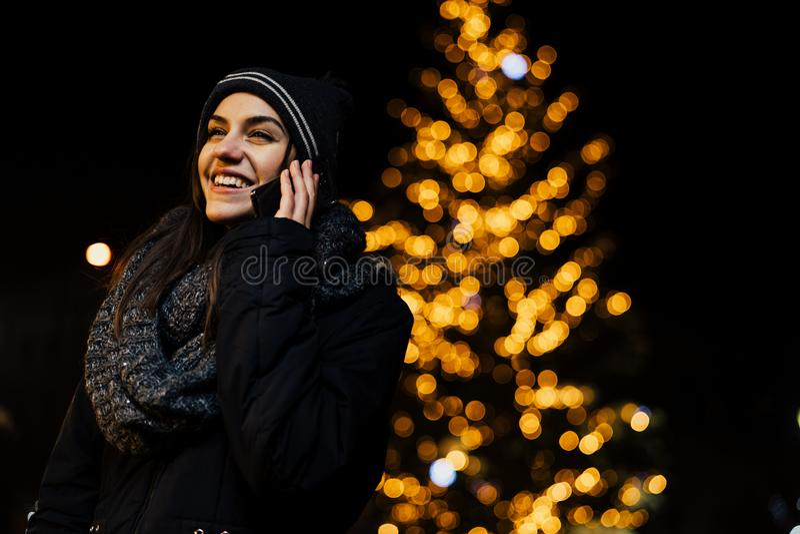 Noc portret piękna brunetki kobieta używa smartphone podczas zimnej zimy w parku Zimy radość chłopiec wakacji lay śniegu zima poz fotografia royalty free
