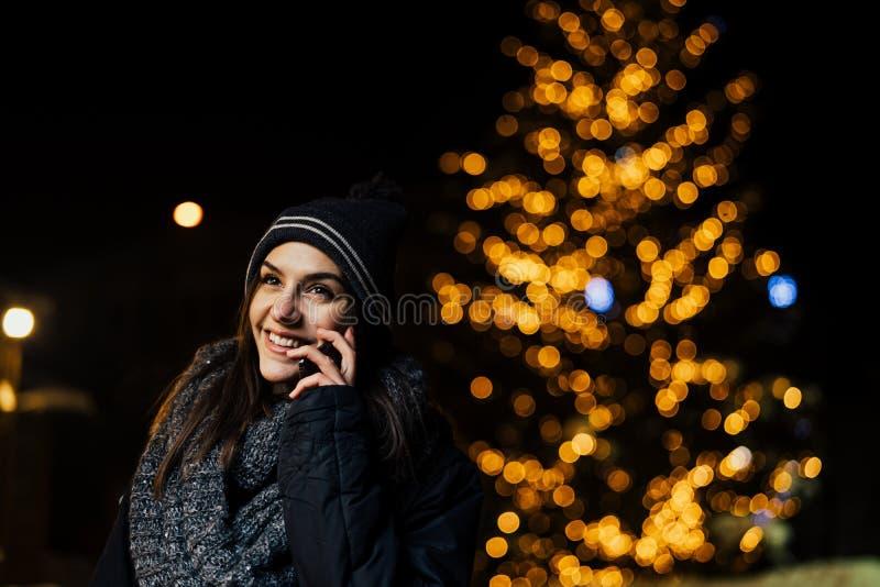 Noc portret piękna brunetki kobieta używa smartphone podczas zimnej zimy w parku Zimy radość chłopiec wakacji lay śniegu zima poz fotografia stock