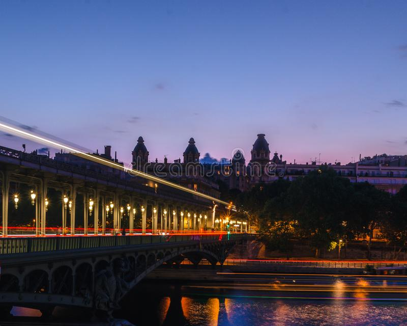 Noc strzał Bir most w Paryż z światłami w długim ujawnieniu czerwień, pomarańcze i kolor żółty, tonuje dawać sensowi moveme obraz stock