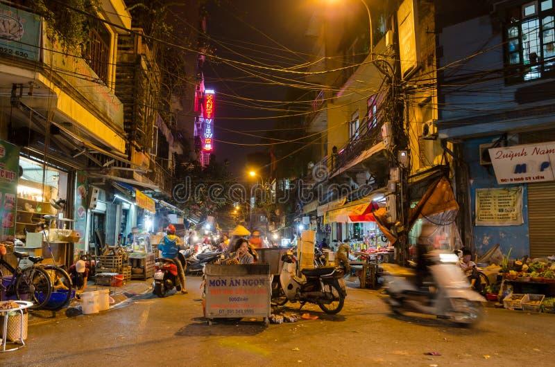 Noc uliczny rynek w Hanoi Starej ćwiartce, ludzie konserwuje widzieć badać wokoło go zdjęcia stock