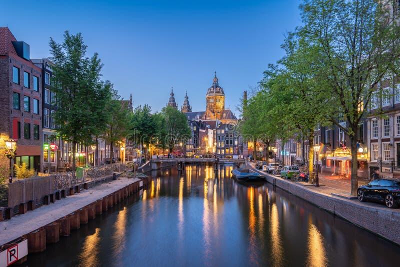 Noc w Amsterdam mieście z Świątobliwym Nicholas kościół przy nocą w Amsterdam, holandie fotografia stock