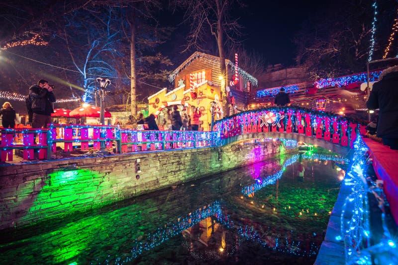 """Noc widok greckich bożych narodzeń """"Oneiroupoli†targowy  z światłami, figurki wokoło rzeki zdjęcia stock"""