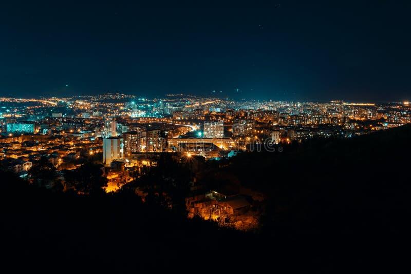 Noc widok od nadmiernego kapitału Gruzja, Tbilisi Latarnie uliczne i wzgórza otacza miasto błękitne niebo - Wizerunek fotografia stock