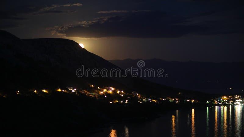 Noc widok pod księżyc światłem na mieście na brzeg Adriatycki morze od skalistego wzgórza w Chorwacja, różny kolor tonuje zdjęcie stock