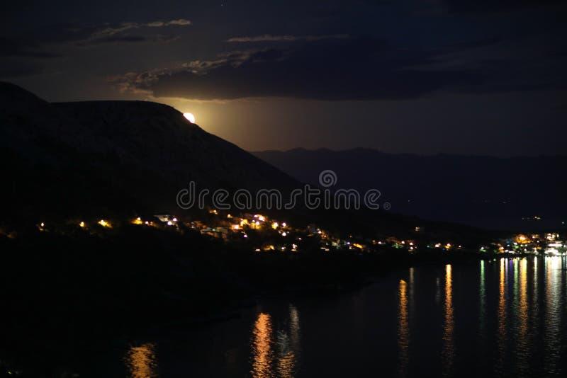 Noc widok pod księżyc światłem na mieście na brzeg Adriatycki morze od skalistego wzgórza w Chorwacja, różny kolor tonuje fotografia royalty free