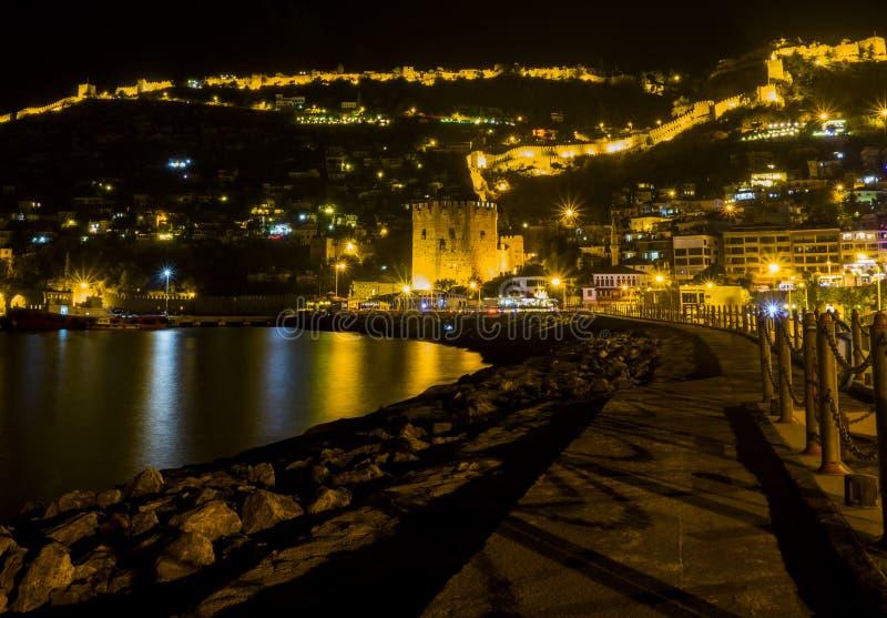 Noc widoku wizerunek stary miasto blisko morza z antycznym kasztelem, domami i kamiennych ścian scenerią między światłami od Alan zdjęcia royalty free