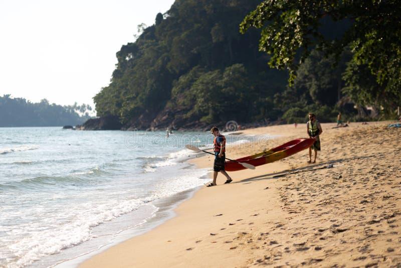 NOCAUTE CHANG, TAILÂNDIA - 9 DE ABRIL DE 2018: Homens que sweaming em um barco do caiaque - praia tropical bonita dos povos do pa imagem de stock royalty free
