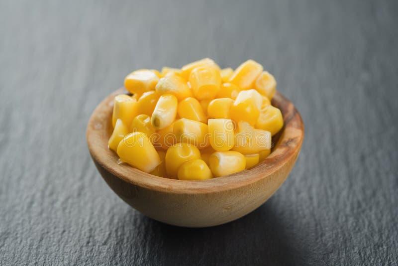 Noccioli di cereale inscatolati in ciotola del woob sul fondo dell'ardesia immagini stock libere da diritti