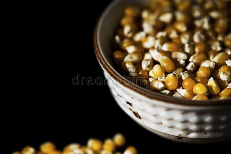 Noccioli di cereale in una ciotola su fondo nero, fine su, isolato fotografia stock