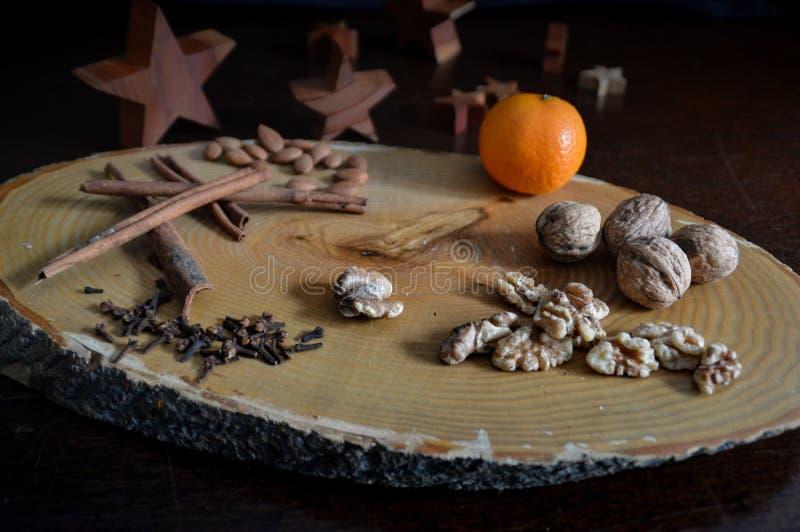 Noccioli, Spezie E Arancione D'Autunno Su Piastra Di Log fotografia stock