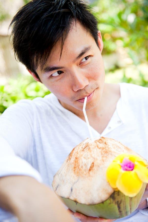 Noce di cocco bevente dell'uomo fotografia stock libera da diritti
