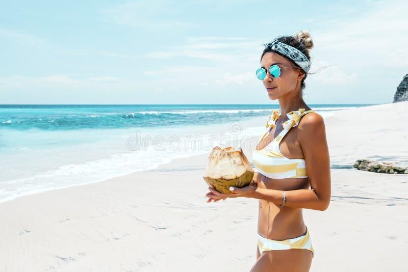 Noce di cocco bevente della donna sulla spiaggia tropicale immagine stock libera da diritti