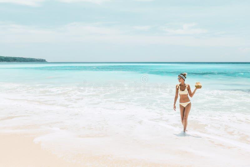 Noce di cocco bevente della donna sulla spiaggia tropicale fotografia stock libera da diritti