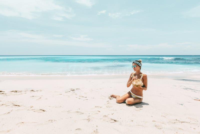 Noce di cocco bevente della donna sulla spiaggia tropicale fotografie stock