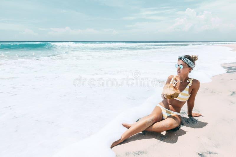 Noce di cocco bevente della donna sulla spiaggia tropicale immagini stock libere da diritti