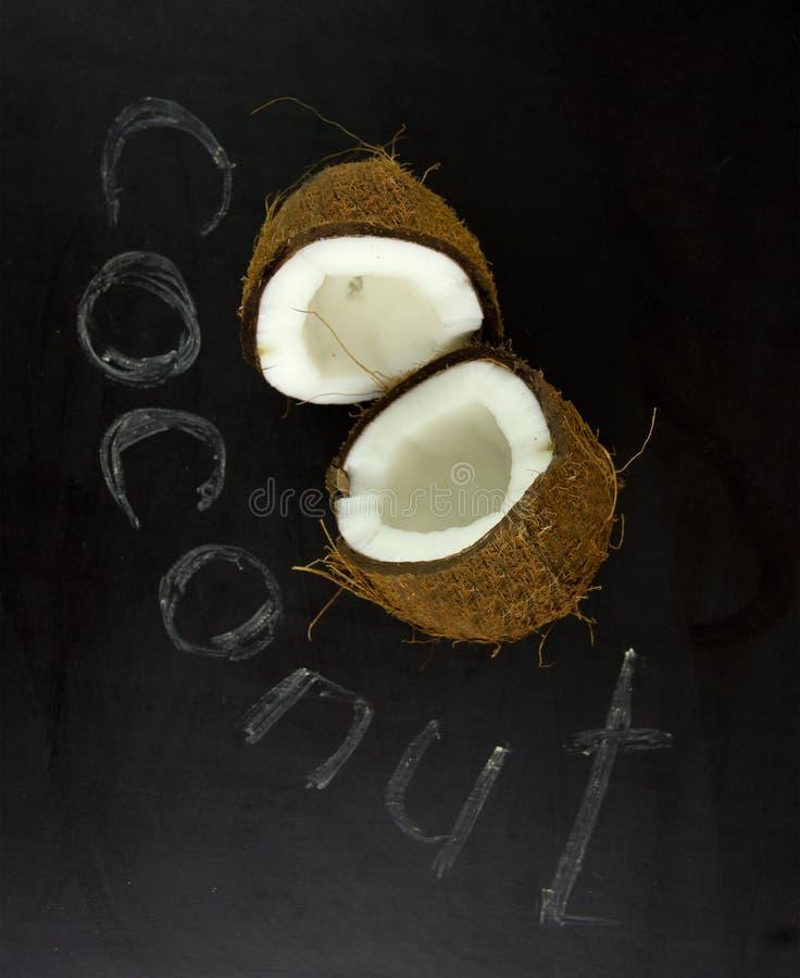 Noce di cocco con la metà su un fondo nero Percorso di ritaglio immagine stock