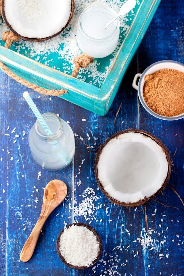 Noce di cocco con olio di cocco, acqua, zucchero ed i fiocchi fotografia stock libera da diritti
