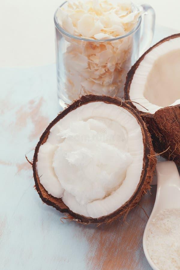 Noce di cocco fresca spaccata in metà, in olio di cocco ed in fiocchi fotografia stock
