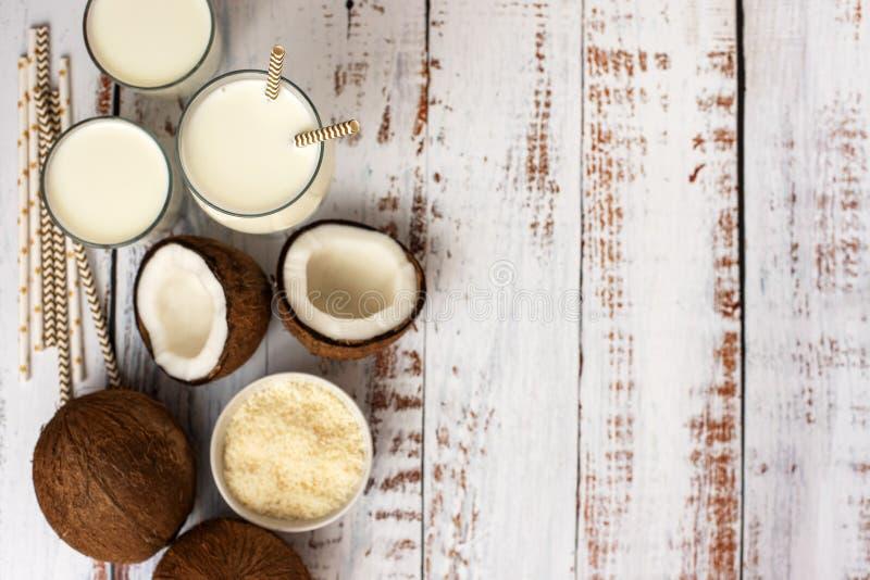 Noce di cocco, vetro di latte di cocco e ciotola con i fiocchi della noce di cocco su un fondo di legno bianco Vista superiore Co fotografie stock libere da diritti