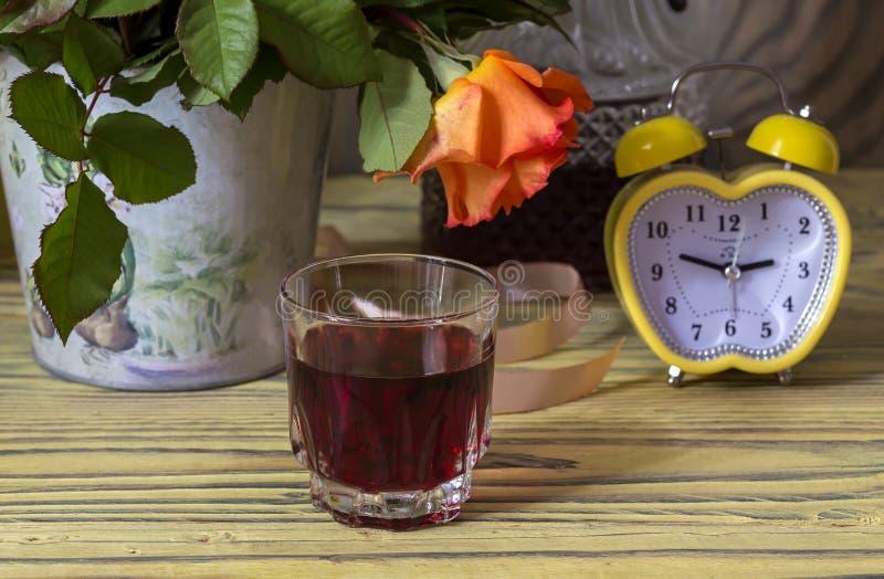 Noch Leben 1 Blumenstrauß von Herbstrosen auf einem Holztisch, einer gelben Uhr und einem Glas der selbst gemachten Weinnahaufnah lizenzfreie stockbilder