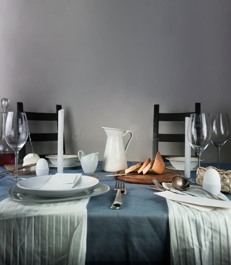 Noch Leben 1 Krug, Gläser, Brötchen, weiße Kerzen auf einer blauen Tischdecke stockfotografie