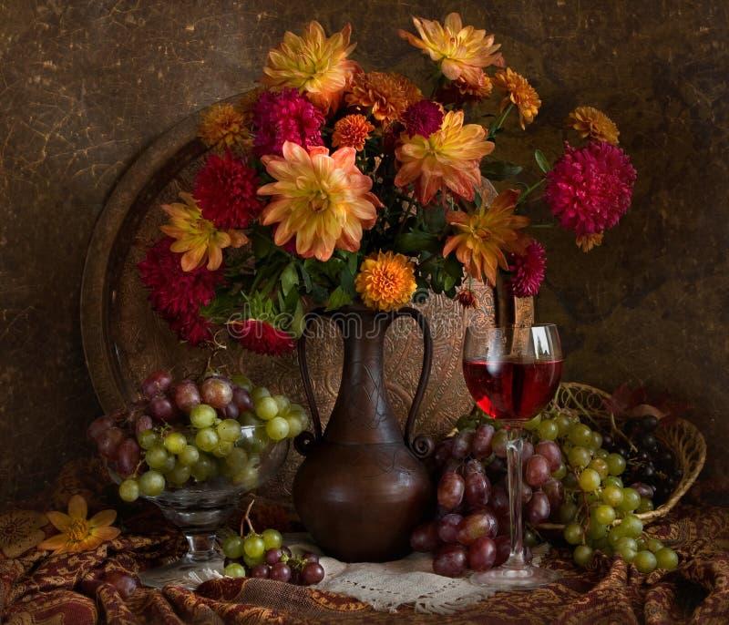 Noch Leben mit Herbstblumen und -wein lizenzfreie stockbilder