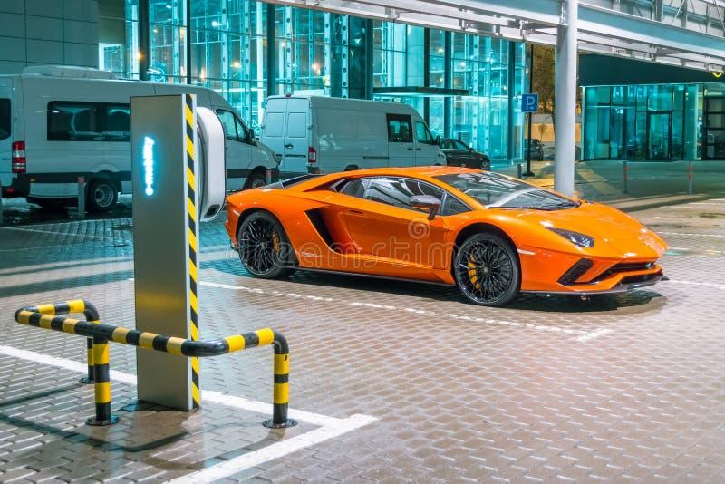 Noche anaranjada de Lamborghini Aventador en las calles que reaprovisionan de combustible para la e-movilidad de los coches eléct foto de archivo libre de regalías